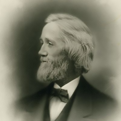 C. Latham Sholes in his later years. Looking away from the camera in this formal studio portrait, he stares hard to the left his hair and beard full and white, in a smart suit and bowtie.