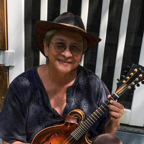 Debra Amesqua wearing a black cowboy hat and a toothy smile holds a mandolin as though she's about to start playing.