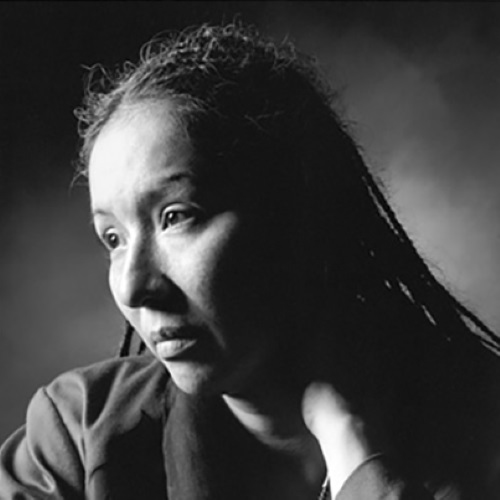 In this atmospheric black and white photo, Ingrid Washinawatok looks down and off to the left away from the camera, her hair in main thin braids draped over her shoulders, and hand placed on her neck.