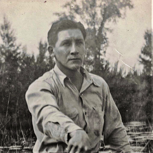 Jerome looking seriously off into the distance while in a canoe. Photograph was taken in 1942 on the Bad River Reservation, probably in the Kakagon sloughs.  He captioned it, The Hunter. You can see his rifle so we know he's out hunting. Based on that and how the rice beds behind him look, likely taken in autumn.