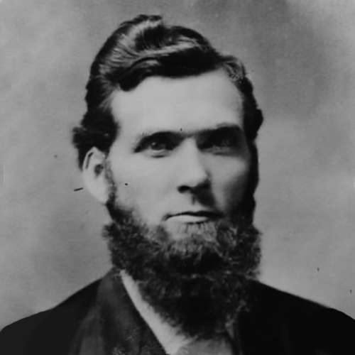 Reverend John W. Carhart, ca. 1880, looks at the camera darkly in this formal studio portrait. His beard is full, and his hair is coiffed longer on top short on the sides. His eyes are overcast but there is a slight smile on his lips.