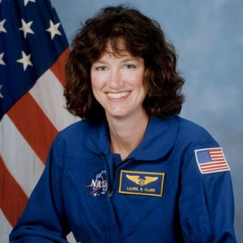 Laurel Clark in her astronaut uniform smiling at the camera with the american flag behind her.