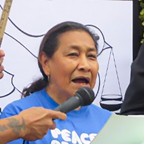 Maria Luis Morales speaking at a demonstration for peace. She's wearing a blue shirt for the demonstration and her dark hair pulled back into a ponytail, scales of justice are visible behind her.