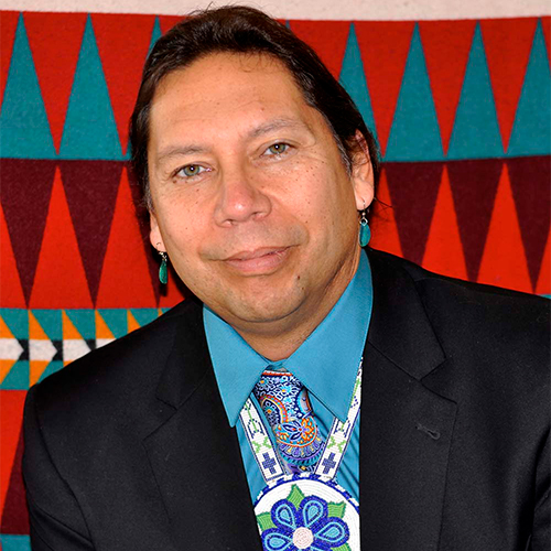 Marin Denning looking at the camera wearing a tradionally beaded neck piece over a paisley print tie and a teal shirt in a black suit jacket. The background is a brightly printed tapestry, with primarily triangle motifies.