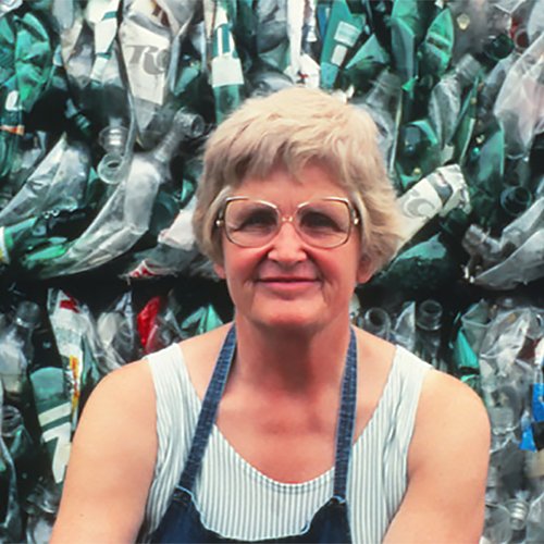 Longtime Sauk County resident Milly Zantow (1923-2014) sits in front of a wall of plastic, crushed into cubes ready to be recycled. She smiles slightly at the camera, wearing glasses, a white tank top, and a blue apron.