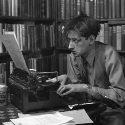 Robert Albert Bloch, author of Psycho, surrounded by tall bookshelves full of books, is sitting in front of a typewriter with an open cigarette case full of cigarettes, a bottle of Wing Fhung Hong, and a pile of papers.