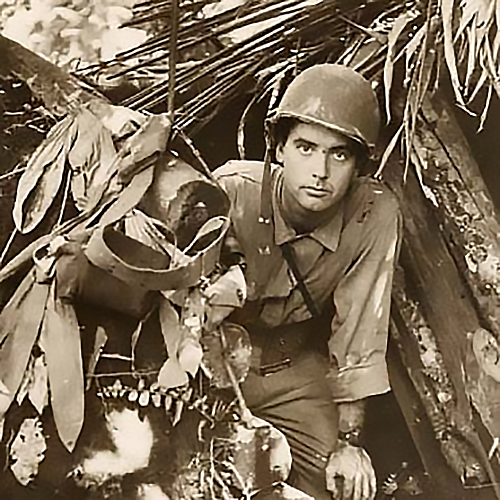 Robert Doyle emerges from a captured Japanese pillbox at Buna, New Guinea, (present day Papua New Guinea). The pillbox is built of dirt, logs and foliage.
