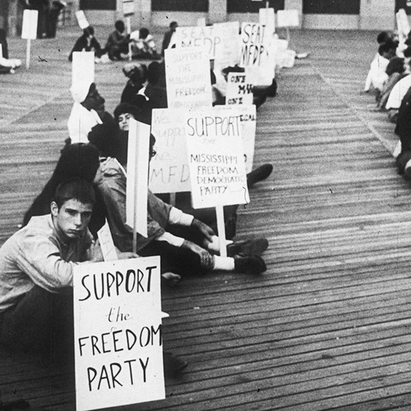 An integrated group of mostly young people sitting on the Atlantic City boardwalk. Many of them are holding signs showing support for the Mississippi Freedom Democratic Party (MFDP).