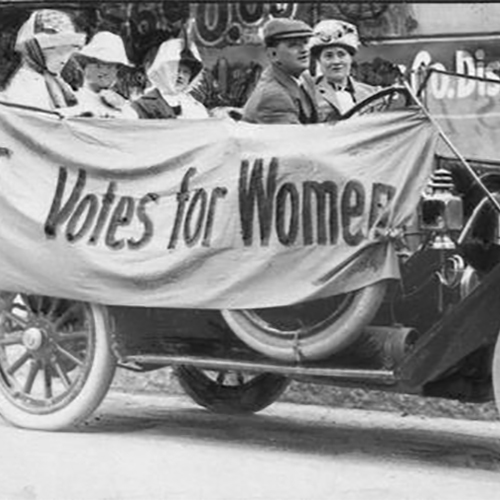 Members of the Political Equality League in an early Ford automobile draped with bunting reading 'Votes for Women.'' In the front seat is Mrs. B.C. Gudden. In the back seat, left to right, are Ruth Fitch, Bertha Pratt King, and Helen Mann.