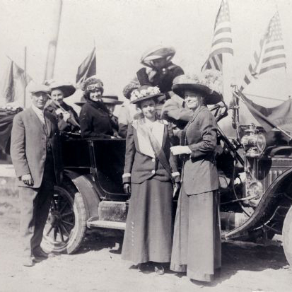 A group of women and one man stand around a car and the US Flag in a black and white photos
