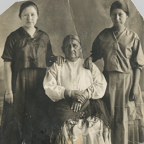 Full-length portrait of two Ho-Chunk women standing on either side of an older Ho-Chunk woman who is sitting. Each woman is wearing a long skirt, a blouse, and jewelry, and the woman sitting also has a shawl on her lap. Both standing women are resting a hand on the seated woman's shoulders.