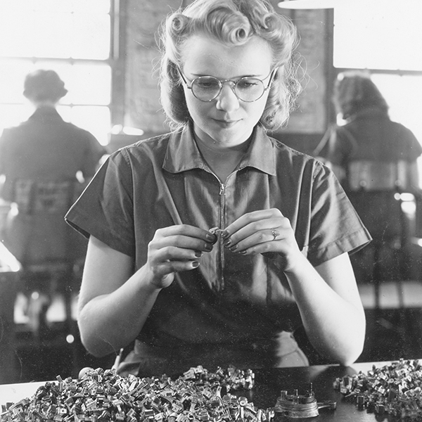 Female worker inspecting small plastic and metal parts at International Harvester's West Pullman Works.