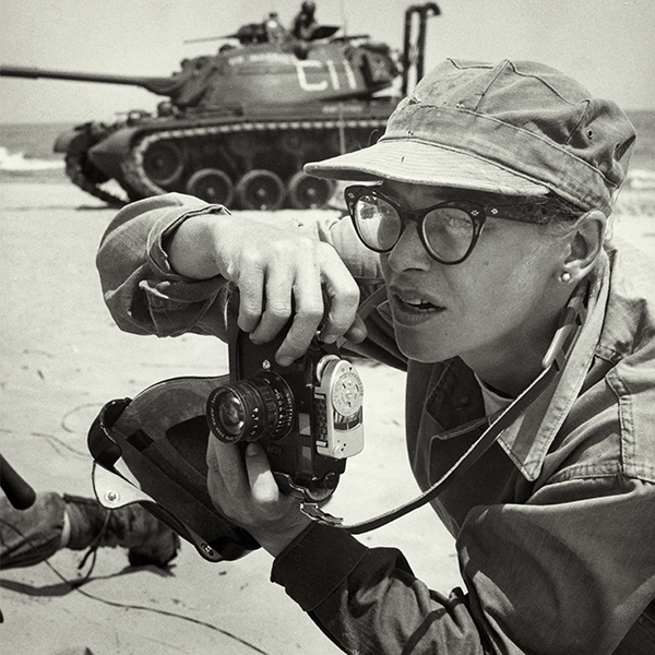 Dickey Chapelle, photographer, on the same Milwaukee beach where she learned to swim as a young girl. She was covering 'Operation Inland Seas' celebrating the opening of the St. Lawrence Seaway. She is holding her camera and there is a tank in the background. This is her favorite photograph of herself at work.