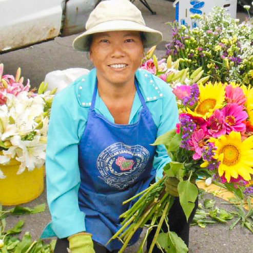 Hmong gardener kneeling and looking into the camera at the Northside Farmer's Market. She is wearing a white hat, light blue shirt, royal blue apron, green gloves, black pants and black sandals. On the apron is the logo for 'The 12 Yang Clan Leaders of Wisconsin, Inc.' In her left hand is a bouquet of flowers, and flowers in buckets surround her.