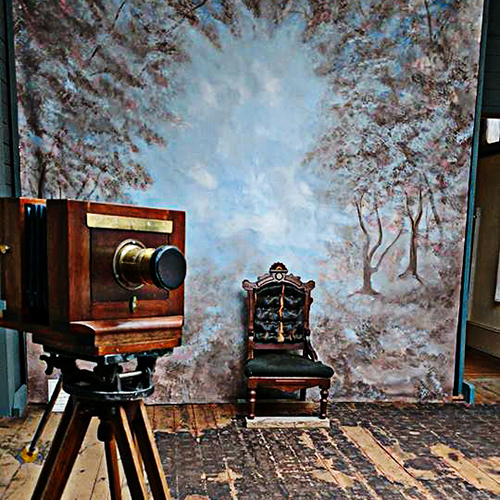 An old fashioned camera is set up facing a dramatic photo backdrop