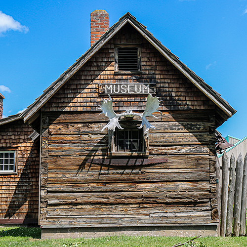 Wood building with antlers attached. A sign reads Museum