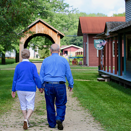 A older white couple holding hands and walking towards the Stonefield buildings