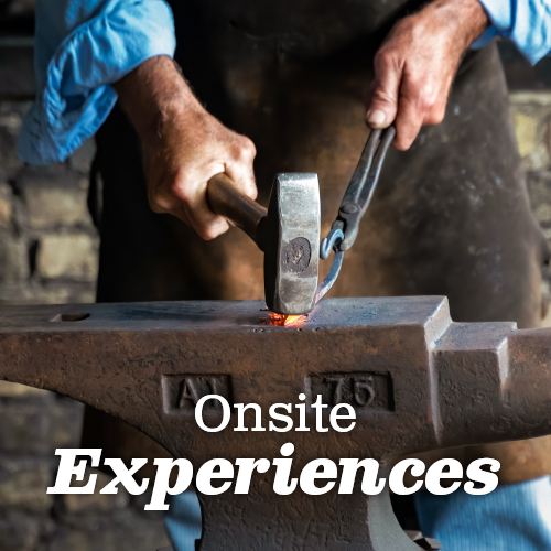 Blacksmith hitting a hook with a metal hammer, a bit of glowing red hot metal sparking where the two pieces meet. Click for Onsite Experiences.